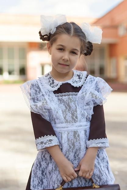 Mała Dziewczynka W Szkolnym Mundurku W Stylu Retro I Białym Fartuchu Idzie Ulicą Z Teczką Po Szkole Premium Zdjęcia