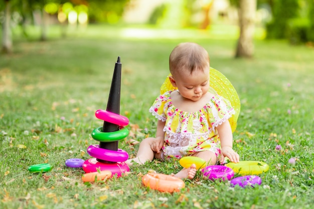 Mała Dziewczynka W Wieku 7 Miesięcy Siedzi Na Zielonej Trawie W żółtej Sukience I Kapeluszu I Bawi Się Piramidą, Wczesny Rozwój Dzieci Do Roku, Spacery Na świeżym Powietrzu Premium Zdjęcia