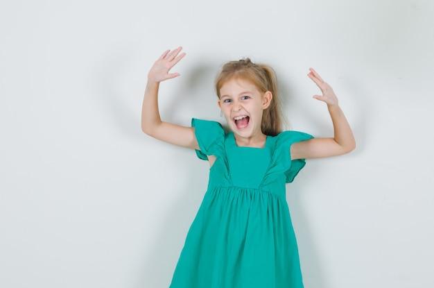 Mała Dziewczynka W Zielonej Sukience Podnosząc Ręce I Krzycząc I Patrząc Energicznie Darmowe Zdjęcia