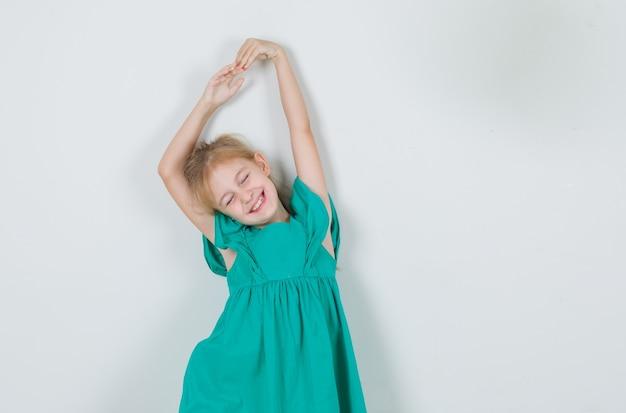 Mała Dziewczynka W Zielonej Sukni, Rozciągając Ramiona Z Zamkniętymi Oczami I Patrząc Wesoło Darmowe Zdjęcia