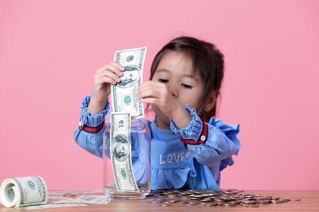 Mała dziewczynka wkłada banknot do słoika z przezroczystego szkła Premium Zdjęcia