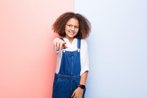 Mała Dziewczynka Wskazując Na Aparat Z Zadowolonym, Pewnym Siebie, Przyjaznym Uśmiechem, Wybierając Cię Ponad ścianą Premium Zdjęcia