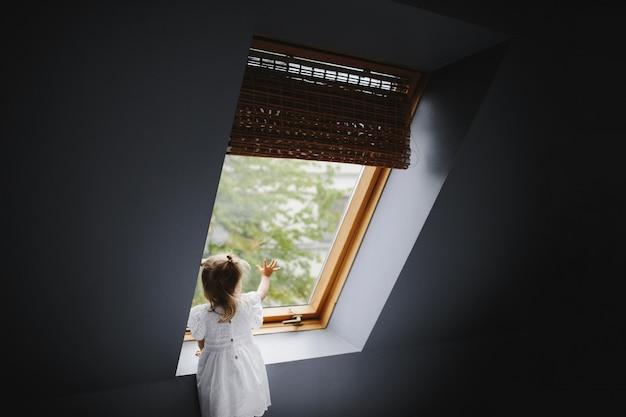 Mała dziewczynka wygląda coś w oknie Darmowe Zdjęcia