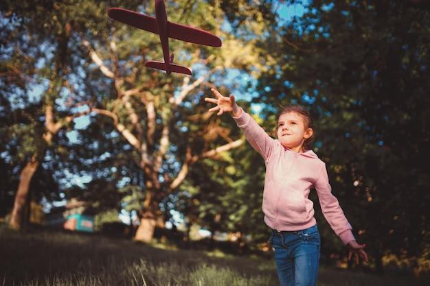 Mała Dziewczynka Wypuszcza Zabawkowy Samolot W Powietrze W Parku Premium Zdjęcia