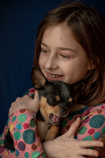 Mała Dziewczynka Z Chihuahua. Dziewczyna Trzyma Chihuahua. Dziewczyna Ze Swoim Zwierzakiem W Ramionach. Chihuahua W Kolorze Czarno Brązowo-białym. Dzieci Kochają Swoje Zwierzęta. Dziewczyna I Chihuahua. Dzieci Kochają Swoje Zwierzęta Premium Zdjęcia