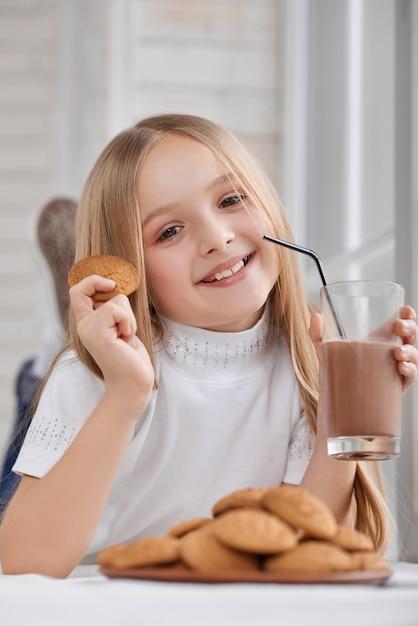 Mała Dziewczynka Z Ciastkami I Czekoladowym Mlekiem Premium Zdjęcia