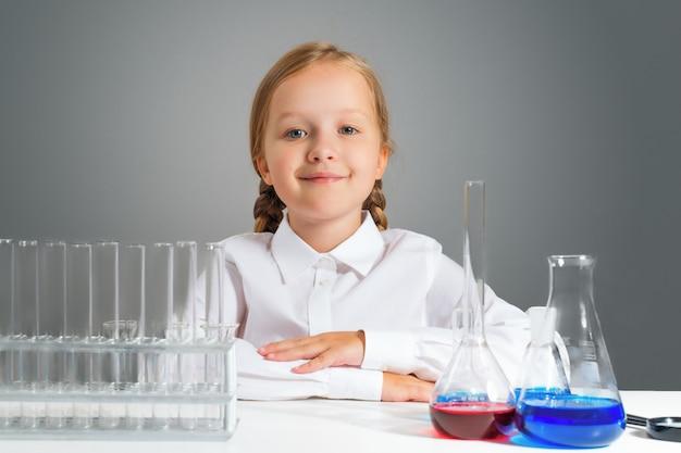 Mała dziewczynka z kolbami dla chemii siedzi przy stołem. Premium Zdjęcia