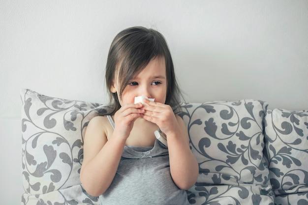 Mała dziewczynka zachorowała. dziecko ma gorączkę. dziecko jest smutne z powodu przeziębienia. Premium Zdjęcia