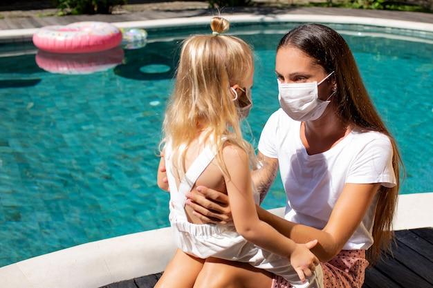Mała Dziewczynka Zakłada Maskę Dla Mamy. Wysokiej Jakości Zdjęcie Darmowe Zdjęcia