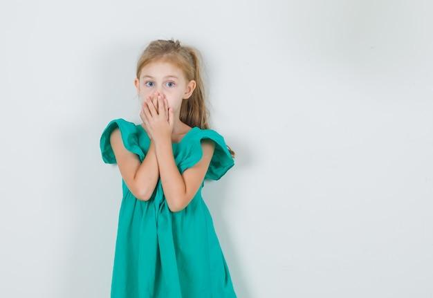 Mała Dziewczynka Zakrywając Usta Rękami W Zielonej Sukience I Patrząc Zaskoczony. Przedni Widok. Darmowe Zdjęcia