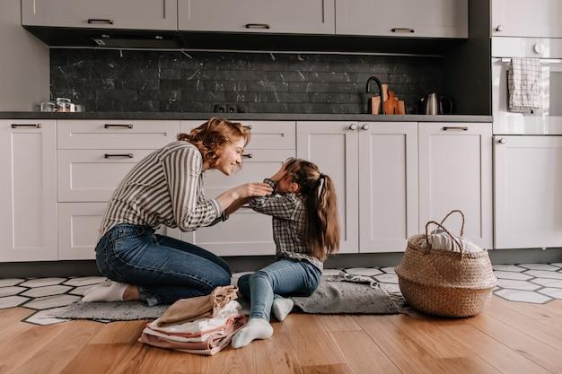 Mała Dziewczynka Zasłoniła Oczy Podczas Zabawy Z Ukochaną Mamą W Kuchni. Darmowe Zdjęcia