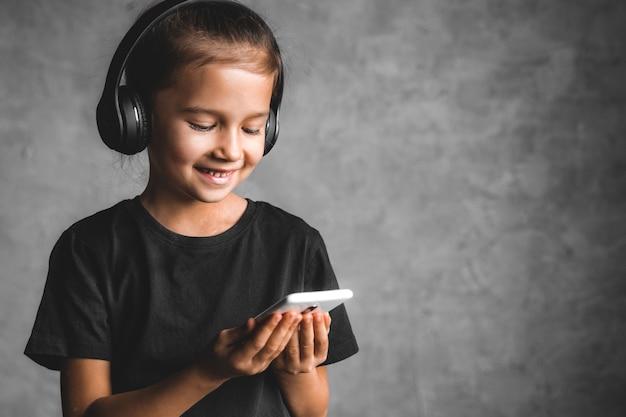 Mała Dziewczynka Ze Słuchawkami I Telefonem Na Szarym Tle Premium Zdjęcia