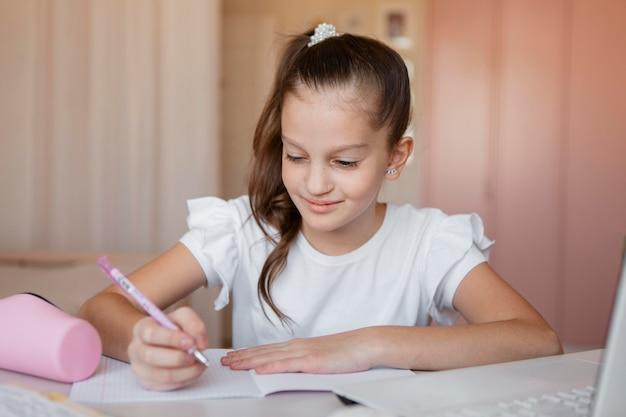 Mała Dziewczynka, Zwracając Uwagę Na Lekcje Online W Domu Premium Zdjęcia