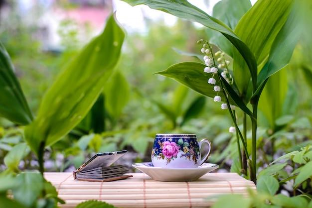 Mała filiżanka herbaty obok kwiatów konwalii Premium Zdjęcia