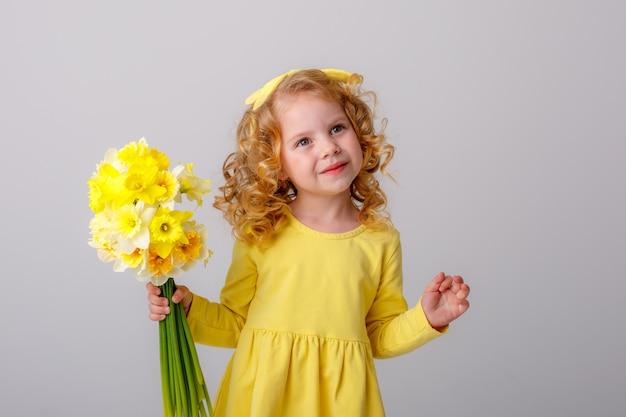 Mała Kędzierzawa Dziewczyna W żółtej Sukience Z Bukietem Wiosennych Kwiatów Na Białej Przestrzeni Uśmiecha Się Premium Zdjęcia