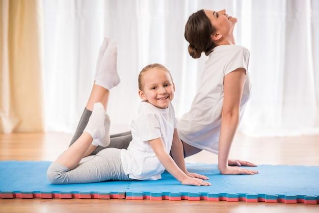 Mała ładna dziewczyna robi joga ćwiczy na dywaniku w domu. Premium Zdjęcia