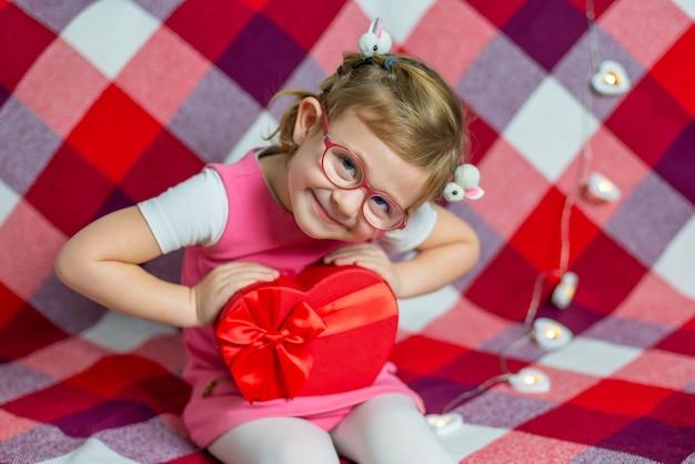 Mała Piękna Dziewczyna W Okularach Z Czerwonym Sercem Pudełko I Balon. święta Walentynkowe. Premium Zdjęcia