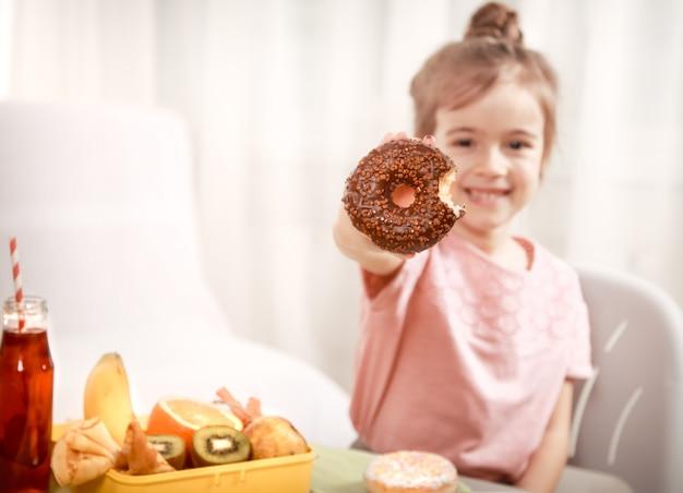 Mała Piękna Rozochocona Dziewczyna Je Pączek Premium Zdjęcia