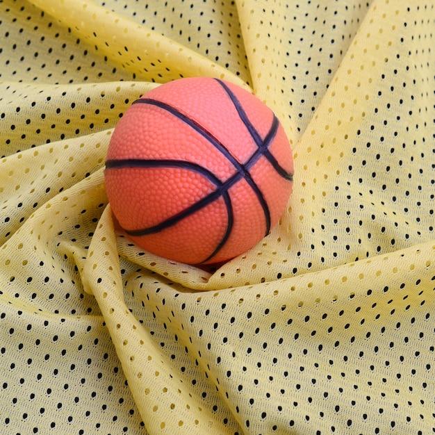Mała pomarańczowa gumowa koszykówka leży na tkaninie odzieży sportowej z żółtego sportowego materiału i tła z wieloma fałdami Premium Zdjęcia