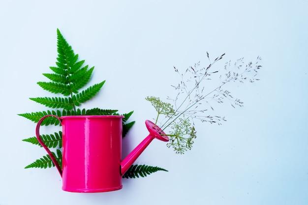 Mała Różowa Konewka Jest Ozdobiona Kwiatami I Ziołami. Pojęcie Ogrodnictwa I Wiejskiego Nastroju. Premium Zdjęcia