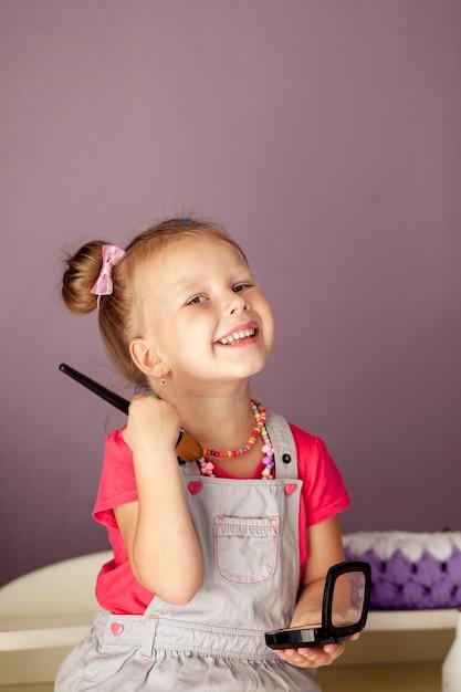 Mała śliczna Blondynka W Wieku 3-4 Lat Siedzi Z Zestawem Kosmetyków I Robi Makijaż Premium Zdjęcia