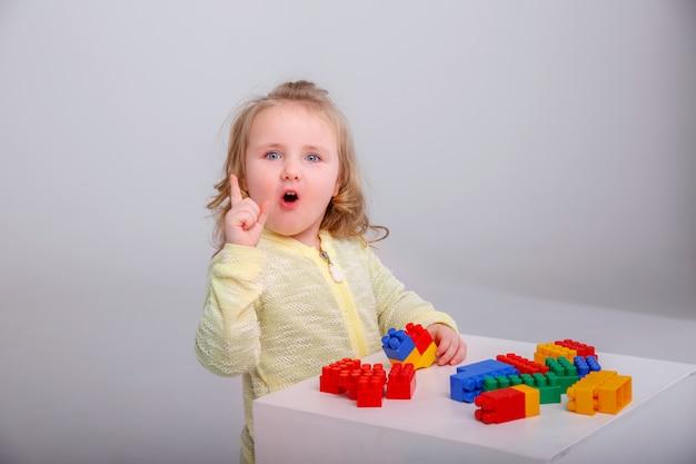 Mała śliczna Blondynki Dziewczyna Bawić Się W Konstruktorze. Pojęcie Edukacji Przedszkolnej Premium Zdjęcia