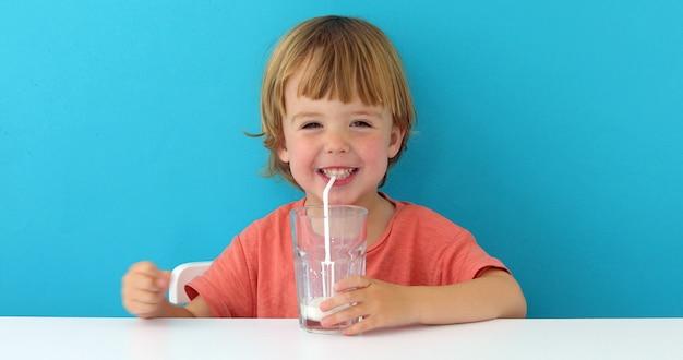 Mała śliczna chłopiec pije mleko Premium Zdjęcia