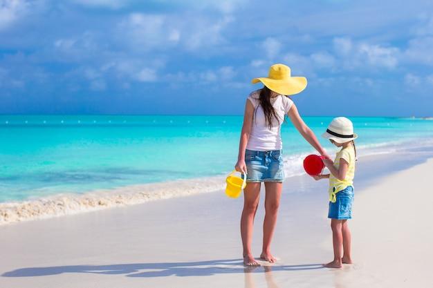 Mała śliczna dziewczyna i potomstwo matka bawić się przy tropikalną plażą Premium Zdjęcia