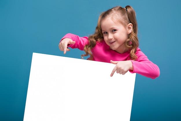 Mała śliczna Dziewczyna W Różowej Koszuli Z Małpimi I Niebieskimi Spodniami Przytrzymuje Puste Puste Tabliczki Premium Zdjęcia