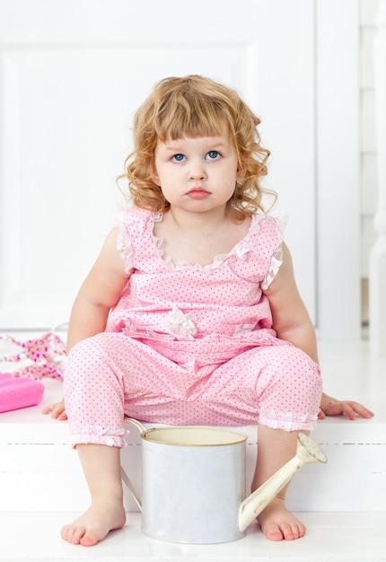 Mała śliczna Kędzierzawa Dziewczyna W Różowej Sukni Z Polek Kropkami Siedzi Na Białym Ganku Stylu Provence Premium Zdjęcia
