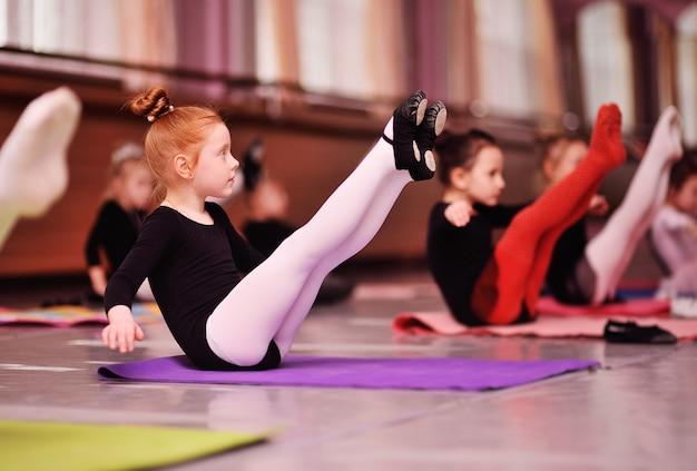 Mała śliczna Rudowłosa Dziewczyna Balerina Wykonuje ćwiczenia Rozciągające W Szkole Baletowej Premium Zdjęcia
