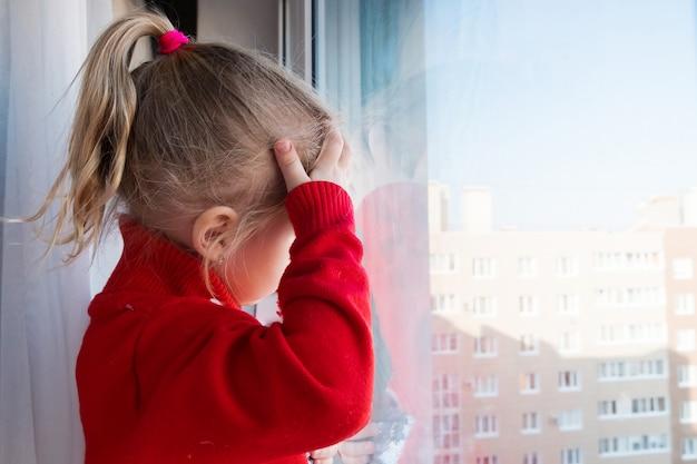 Mała Smutna Dziewczyna Patrzeje Przez Okno. Pozostań W Kwarantannie Domowej. Koncepcja Izolacji. Epidemia Wirusowa, Kryzys Medyczny Premium Zdjęcia