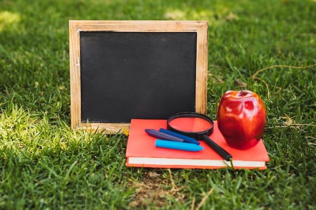 Mała tablica i materiały piśmienne z jabłkiem na trawie Darmowe Zdjęcia