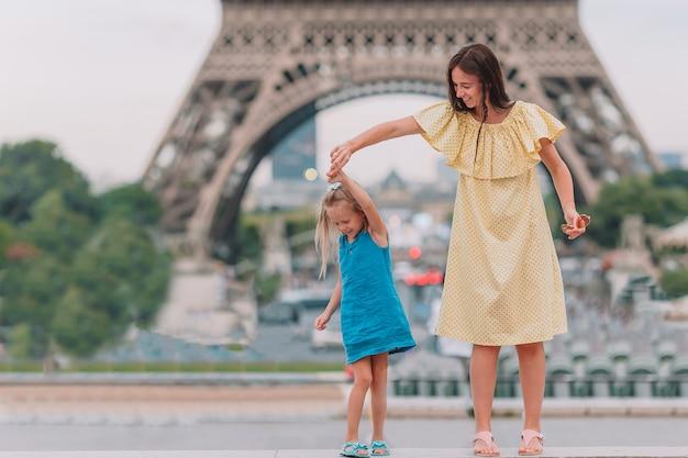 Mała urocza dziewczyna i jej młoda mama w paryskiej pobliskiej wieży eifla podczas wakacje Premium Zdjęcia
