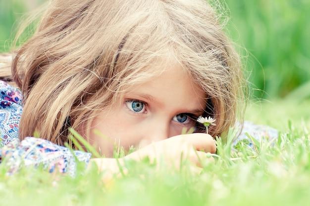 Mała Urocza Dziewczyna, Leżąc Na Trawie Patrząc Na Stokrotkę Darmowe Zdjęcia