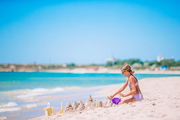 Mała Urocza Dziewczyna Na Tropikalnej Plaży Co Zamek Z Piasku Premium Zdjęcia