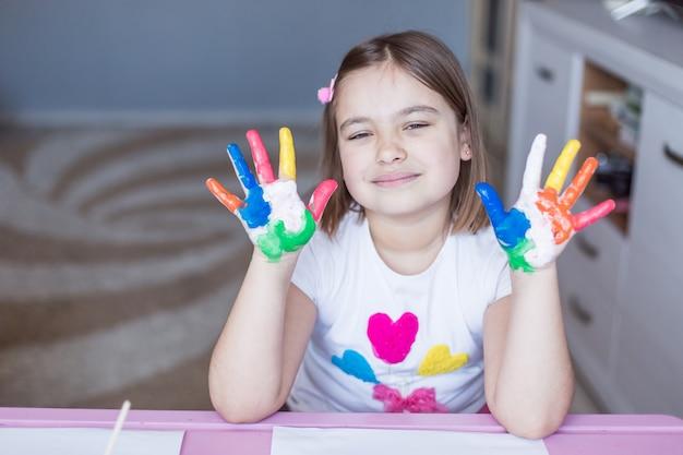 Mała Urocza śliczna Rozochocona Radosna Dziewczyna Rysuje Samotnie W Domu Podczas Wakacji Lub Kwarantanny. Domowa Aktywność Dzieciństwa W Domu, Sztuka Dla Dzieci Premium Zdjęcia