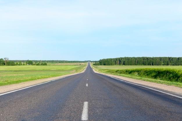 Mała Wiejska Droga Asfaltowa. Krajobraz Z Niebieskim Niebem, Trawą I Drzewami. Po Jezdni Jeżdżą Samochody Premium Zdjęcia