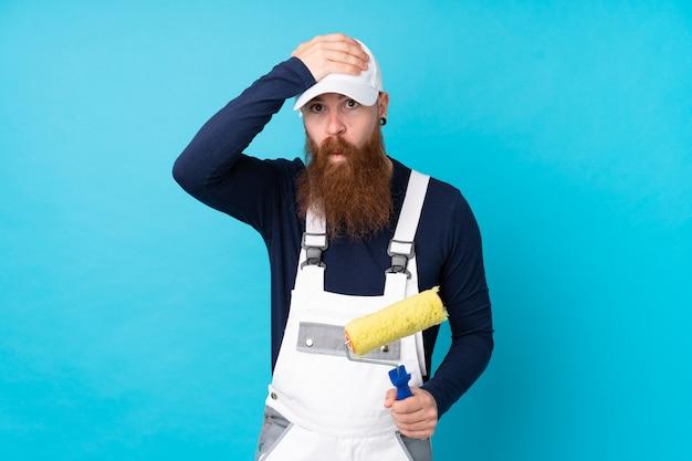 Malarz Mężczyzna Z Długą Brodą Na Pojedyncze Niebieskie ściany Z Zaskoczenia Wyraz Twarzy Premium Zdjęcia