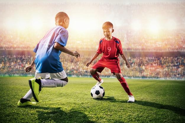 Małe azjatyckie dzieci w piłce nożnej w akcji na stadionie Premium Zdjęcia