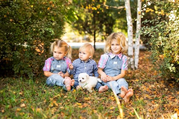 Małe Blondynki I Chłopiec Bawi Się W Ogrodzie Ze ślicznym Białym Szczeniakiem Premium Zdjęcia