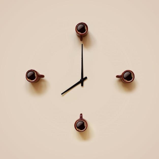 Małe brązowe kubki z kawą i czarnymi wskaźnikami umieszczonymi jak tarcza zegara Premium Zdjęcia