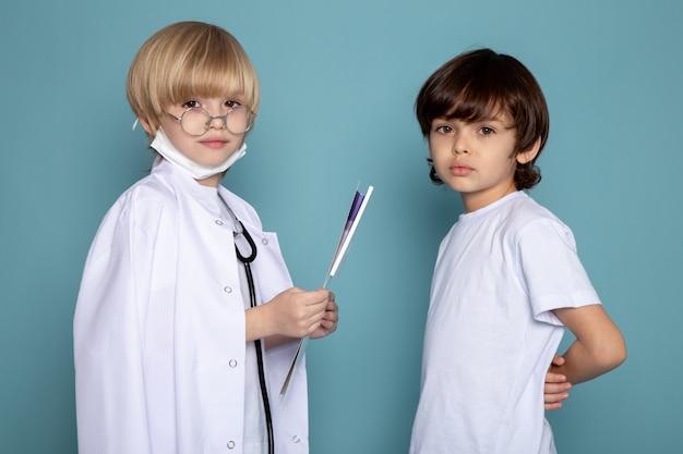 Małe Dzieci Słodkie Urocze, Patrząc Na Kamery, Jeden W Białym Garniturze Lekarza, A Drugi W Białej Koszulce Na Niebieskiej ścianie Darmowe Zdjęcia