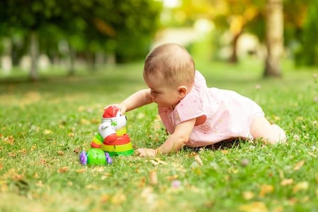 Małe Dziecko Bawi Się Latem W Piramidę Na Zielonej Trawie Premium Zdjęcia