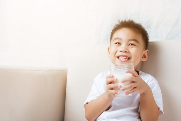 Małe Dziecko Chłopiec Ręka Trzyma Dojnego Szkło On Pije Bielu Mleko Premium Zdjęcia