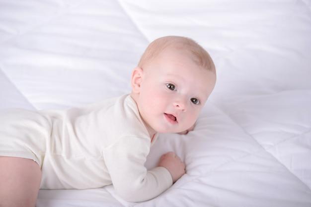Małe dziecko czołga się na białym łóżku. Premium Zdjęcia