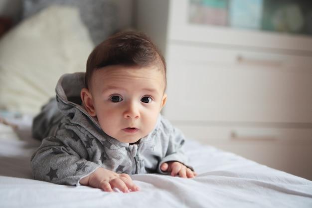 Małe Dziecko Czołgające Się Na łóżku W Białym Pokoju. Na Jego Twarzy Zainteresowanie I Zastanawianie Się. Europejski. Premium Zdjęcia