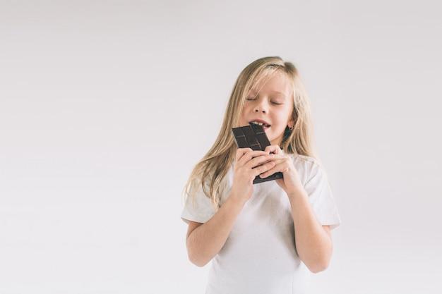 Małe Dziecko Je Czekoladowego Bar. Blondy Dziewczyna Odizolowywająca Na Bielu. Premium Zdjęcia