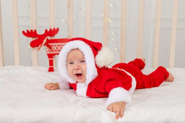 Małe Dziecko Leży W łóżeczku W Stroju świętego Mikołaja I Płacze Premium Zdjęcia