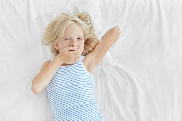Małe Dziecko O Blond Włosach, Niebieskich Oczach I Piegowatej Skórze, Leżące W łóżku, Zakrywające Usta Ręką I Ziewające. Urocza Mała Dziewczynka Budzi Się Rano, Ma Senny Wyraz Twarzy Po śnie Darmowe Zdjęcia